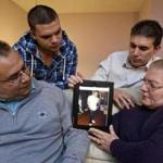 1/5/2012 Saugus, MA Rev Juarez Goncalves (cq) with his wife, Rev Clauri Goncalves (cq) and their son's Joao Marcos Goncalves (cq)(back left) and Guilherme Goncalves (cq) looking at a photo of their middle son, Samuel Goncalves who died in in October after a bout with cancer in the families living room on Thursday January 5, 2011. (Matthew J. Lee/Globe staff) slug: 06insurance section: metro Reporter: